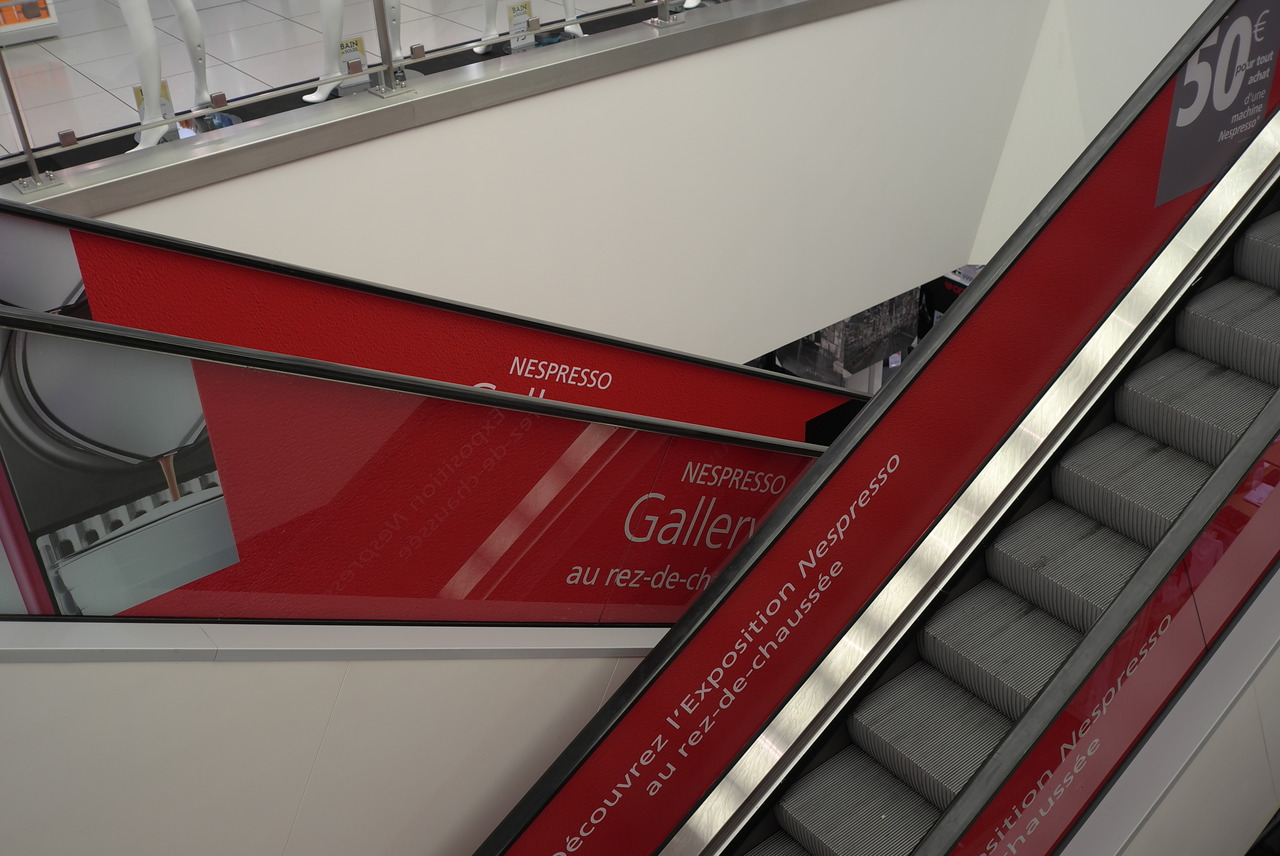 Création, fabrication et installation des habillages d'escalators dans les grands magasins pour Nespresso.